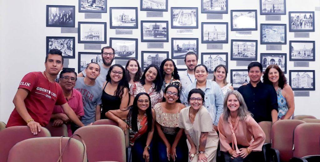 Na imagem, há uma parede branca decorada com quadros, dezessete pessoas, entre estudantes indígenas, as equipes de servidoras técnicas e professoras do NUEI/SIPAD e da PRAE, que participaram do acolhimento de estudantes indígenas, ocorrido na Sala da Memória do prédio Histórico da UFPR.